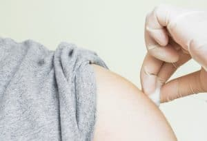 A pharmacist holding a cotton ball to a patients arm following the flu shot