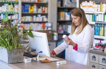 Female pharmacist checking a prescription transfer on the computer