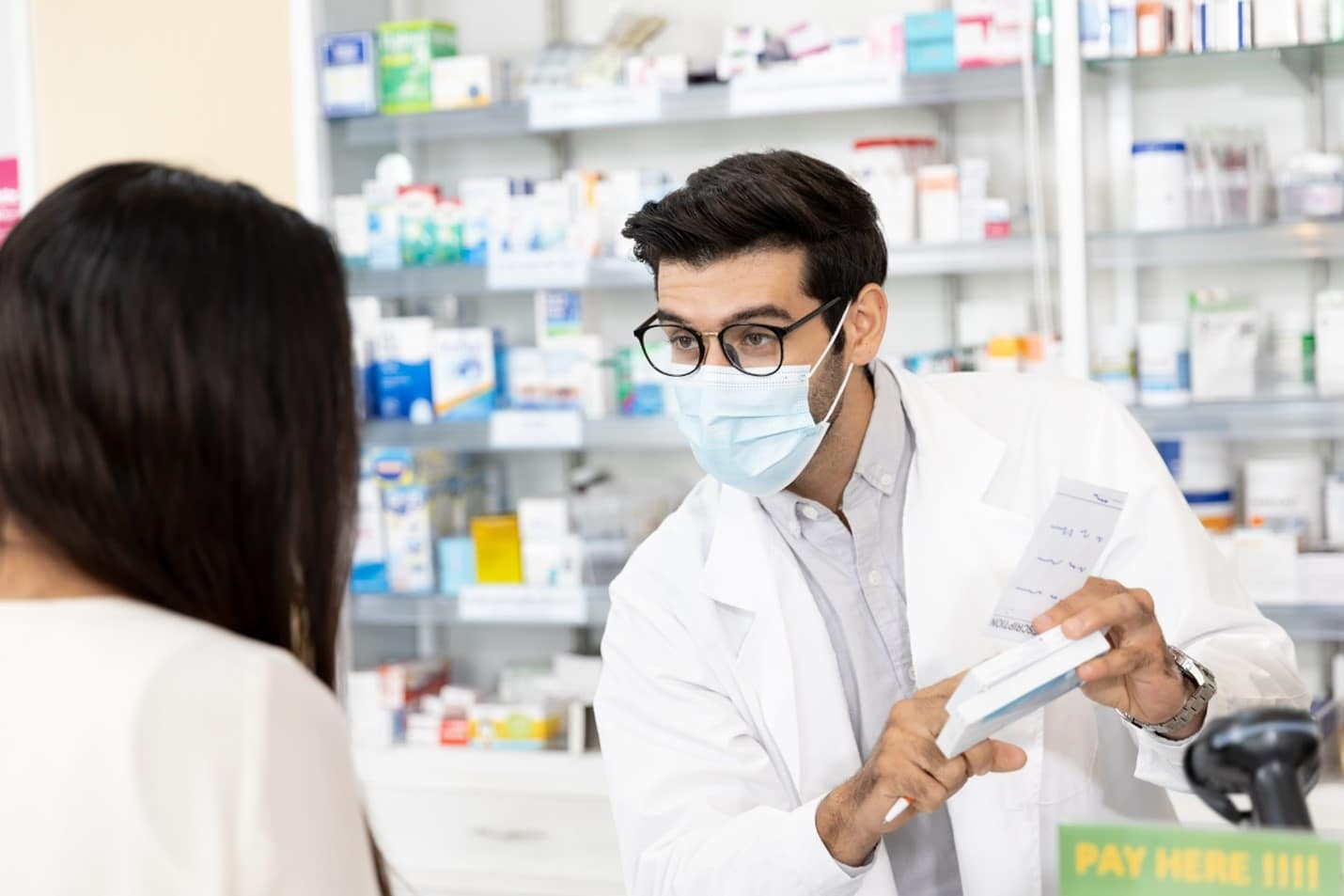 Pharmacist explaining a medication to a customer.