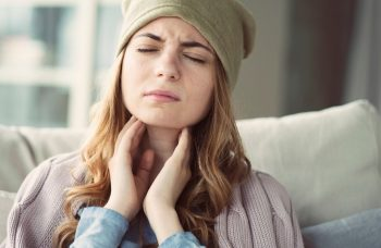 Woman holding her throat with discomfort.