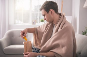 Person checking their delivered prescription while sitting on the couch with a blanket over their shoulders.