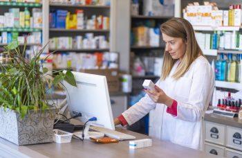 Female pharmacist checking a prescription transfer on the computer